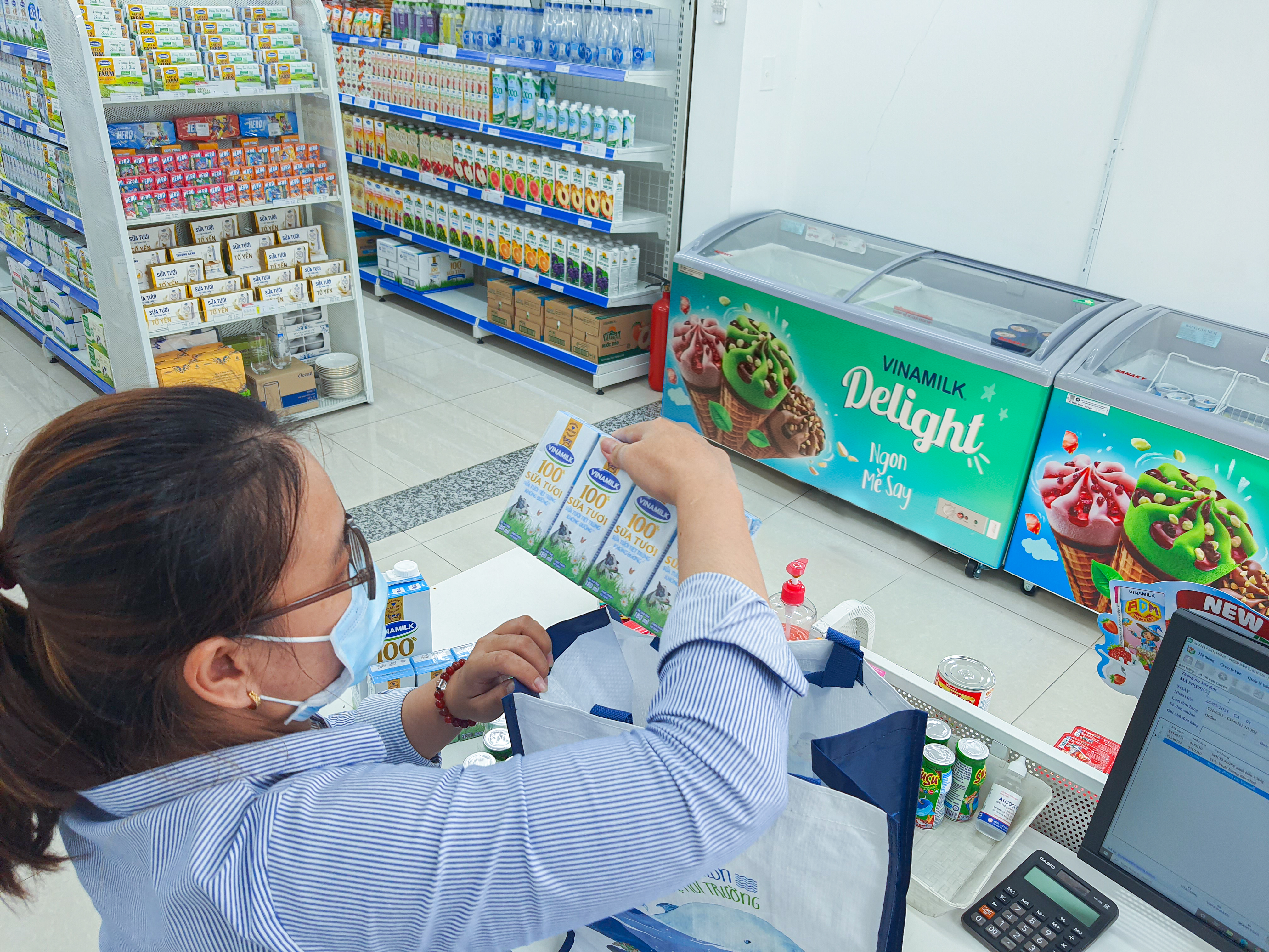 """Nhân viên của cửa hàng """"Giấc mơ sữa Việt"""" cẩn thận kiểm tra các sản phẩm trước khi giao đến tận nhà cho người tiêu dùng."""