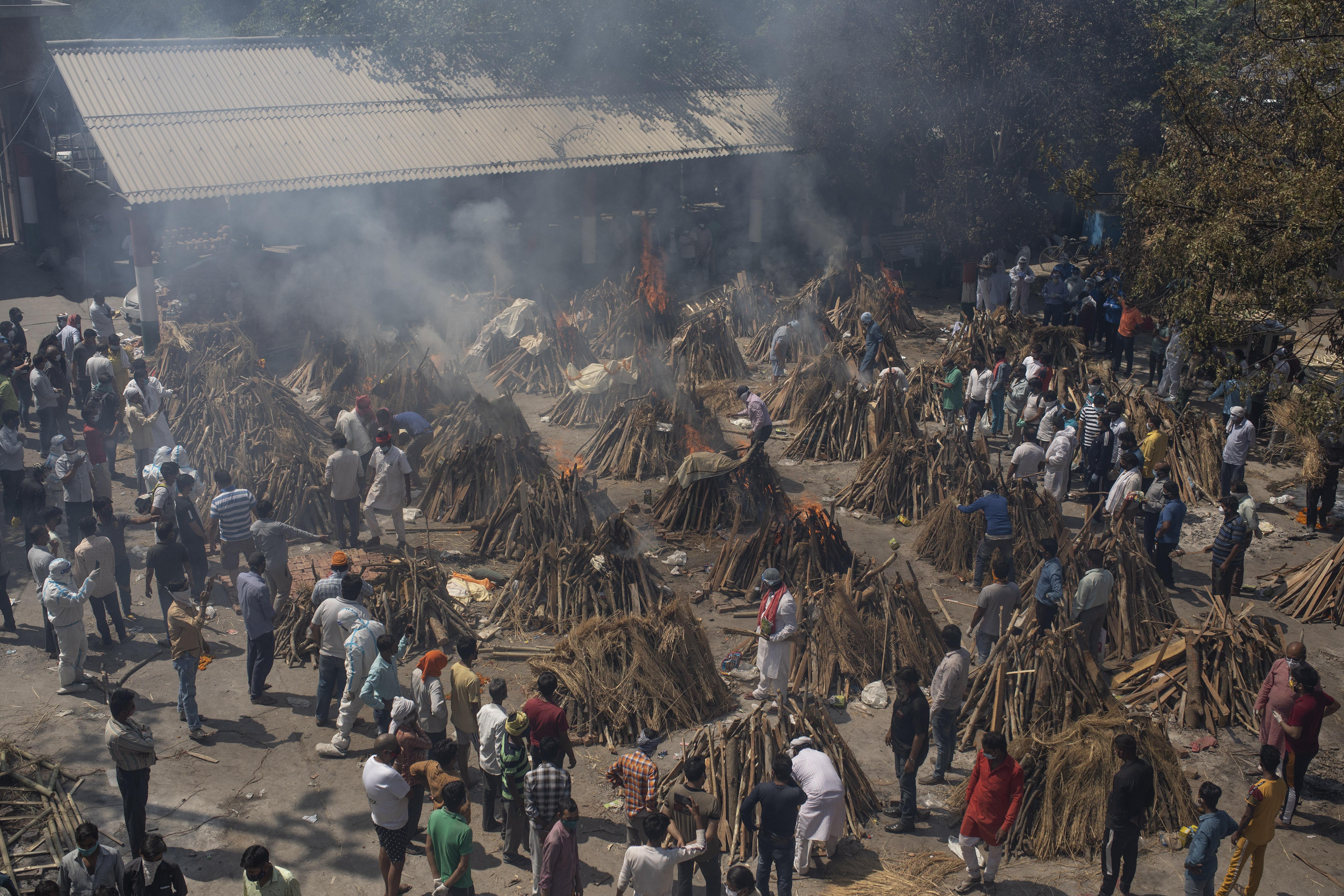 Những giàn hỏa táng người chết vì Covid-19 được dựng lên tại một khu đất trống - nơi trở thành giàn hỏa táng hàng loạt của bệnh nhân Covid-19 ở New Delhi, Ấn Độ - Ảnh: Altaf Qadri/AP