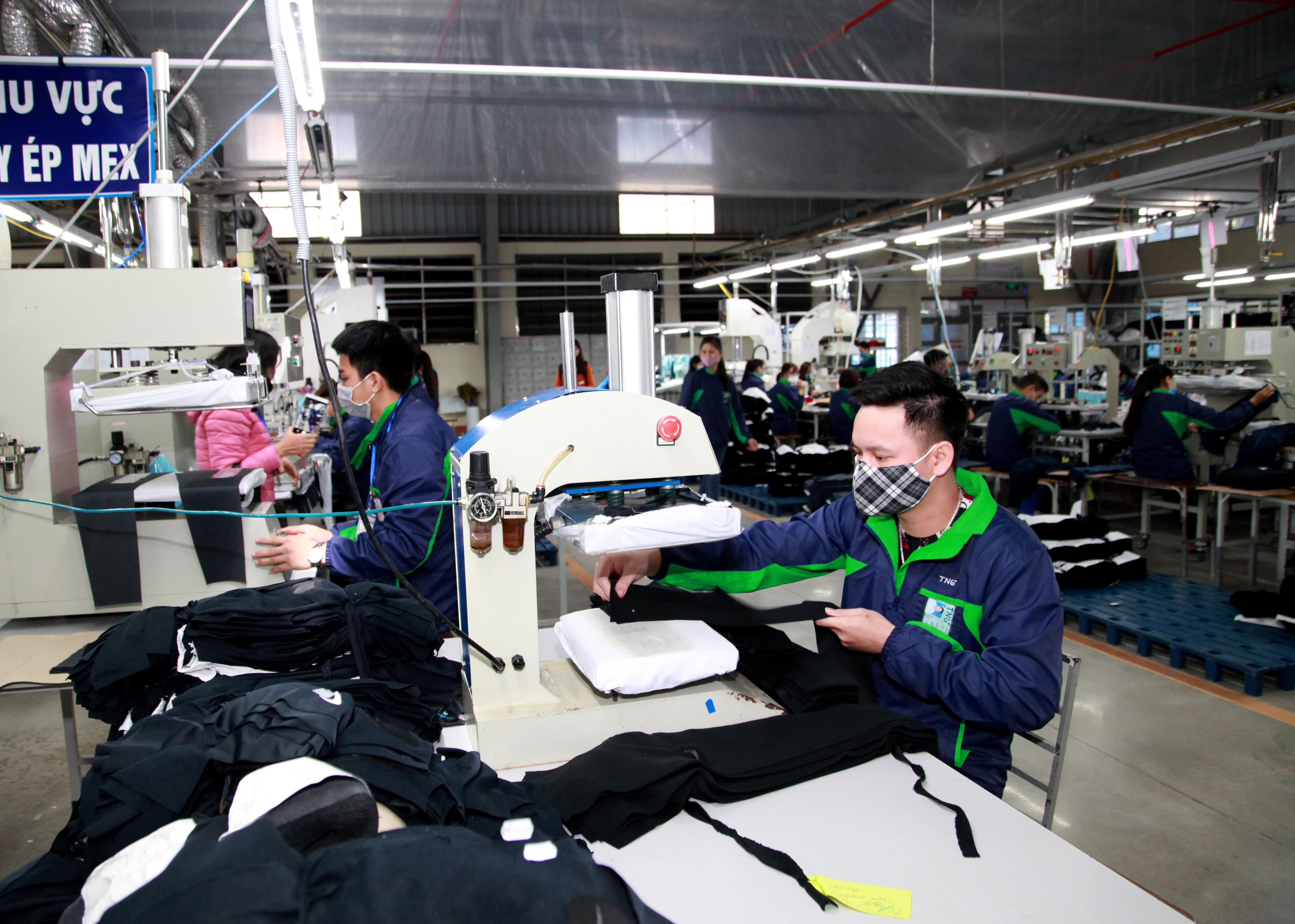 Công nhân một doanh nghiệp chuyên sản xuất hàng may mặc. Ảnh - Mạnh Dũng.