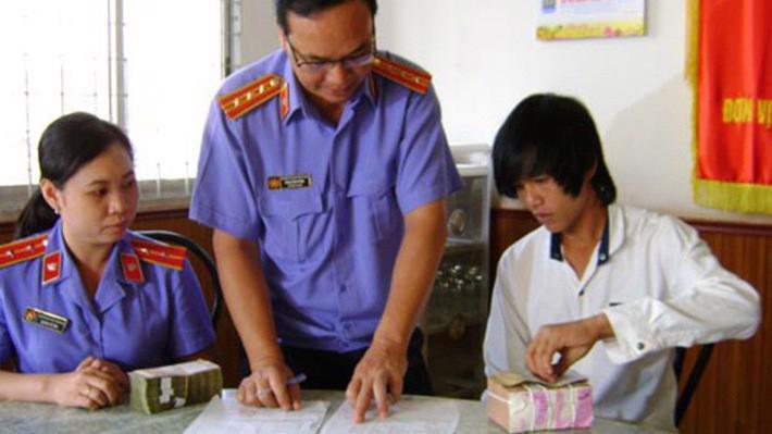 Đại diện Viện Kiểm sát nhân dân Sóc Trăng tiến hành thủ tục bồi thường oan sai cho một công dân - Ảnh: Phong Trinh.