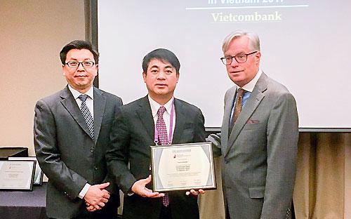 Ông Nghiêm Xuân Thành (giữa), Chủ tịch Hội đồng Quản trị Vietcombank nhận giải thưởng từ The Asian Banker.<br>