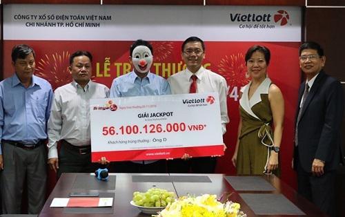 Một người trúng giải xổ số của Vietlott đeo mặt nạ nhận thưởng.