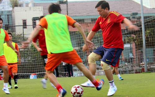 Bộ trưởng Đinh La Thăng (áo đỏ, bên phải) trong một lần đích thân xỏ giày ra sân bóng với vai trò tiền đạo, trong trận đấu giữa hai đội Văn phòng Bộ Giao thông Vận tải và FC Phóng viên, tháng 11/2013 - Ảnh: FC Phóng viên.