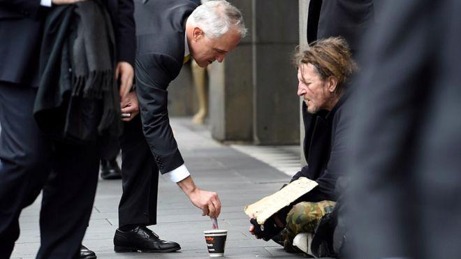 Thủ tướng Australia Malcom Turbull cho tiền người ăn xin trên đường phố Melbourne, ngày 18/8 - Ảnh: Reuters.<br>