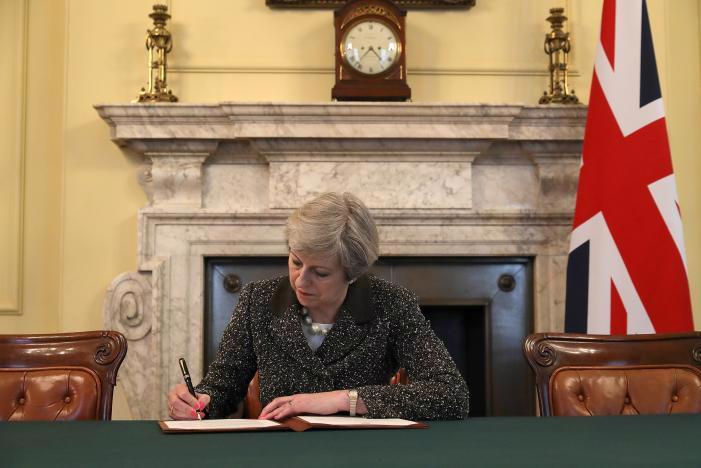 Thủ tướng Anh Theresa May ký lá thư gửi Chủ tịch Hội đồng EU Donald Tusk để kích hoạt Điều 50 Hiệp ước Lisbon, nhằm khởi động tiến trình đưa Anh ra khỏi EU, ngày 28/3 tại Văn phòng Nội các Anh ở London - Ảnh: Reuters.<br>