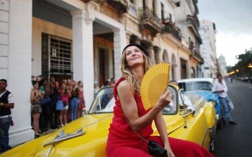 Siêu mẫu Gisele Bundchen tạo dáng bên một chiếc xe cổ trước buổi trình diễn của Chanel ở Havana - Ảnh: Reuters/BBC.<br>