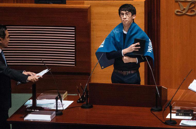 """Nghị sỹ Sixtus """"Baggio"""" Leung của Hồng Kông mang một tấm băng rôn ghi dòng chữ """"Hồng Kông không phải là Trung Quốc"""" khi tuyên thệ hôm 12/10 - Ảnh: Bloomberg.<br>"""