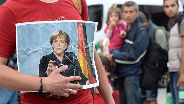 Ảnh Thủ tướng Đức Angela Merkel trên tay một người di cư tới Đức - Ảnh: Getty/Express.<br>