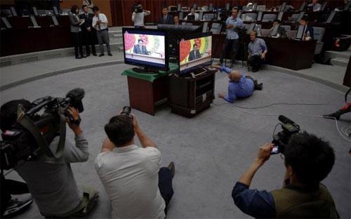 Các nhà báo quốc tế tác nghiệp quanh màn hình phát trực tiếp bài phát biểu của nhà lãnh đạo Triều Tiên Kim Jong Un tại Đại hội Đảng Lao động nước này ngày 8/5 - Ảnh: Reuters.<br>