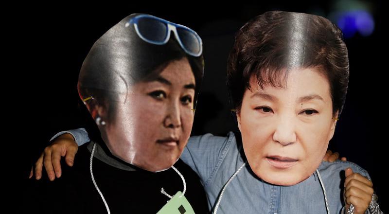 Người biểu tình ở Seoul, Hàn Quốc đeo mặt nạ cắt từ ảnh của bà Choi Soon-sil (trái) và ảnh cuẩ Tổng thống Park Geun-hye - Ảnh: Reuters.<br>