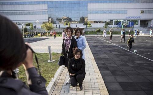 Các cô gái trẻ đang chụp ảnh trước bách hóa Pothonggang ở Bình Nhưỡng - Ảnh: Reuters.<br>