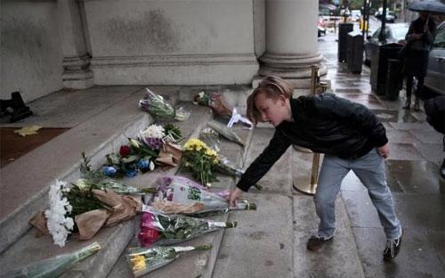 Một cậu bé đặt hoa tưởng niệm các nạn nhân vụ khủng bố Paris trước cửa Đại sứ quán Pháp ở London, Anh sáng ngày 14/11 - Ảnh: Reuters.<br>