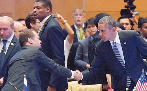 Thủ tướng Nga Dmitry Medvedev (trái) bắt tay với Tổng thống Mỹ Barack Obama (phải) tại Kuala Lumpur ngày 22/11 - Ảnh: Reuters.<br>