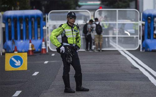 Một viên cảnh sát đứng gác trên đường phố Hồng Kông ngày 16/5 - Ảnh: Bloomberg.<br>