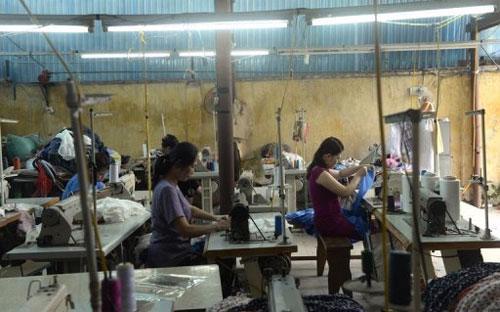Nữ công nhân làm việc trong một xưởng may nhỏ ở ngoại ô Hà Nội hôm 2/5/2013 - Ảnh: AFP.<br>