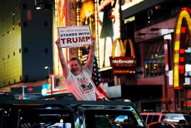 Một người ủng hộ Donald Trump vui mừng trên Quảng trường Thời đại ở New York sau khi Trump chiến thắng đêm 8/11 - Ảnh: Reuters.<br>