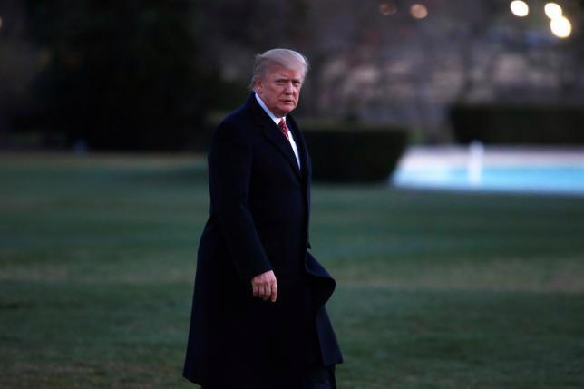 Tổng thống Mỹ Donald Trump bước vào Nhà Trắng sau khi xuống máy bay Marine One ngày 27/3 - Ảnh: Reuters.