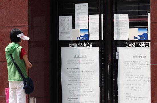 Thông báo đóng cửa bên ngoài một ngân hàng tiết kiệm ở Seoul - Ảnh: Bloomberg.
