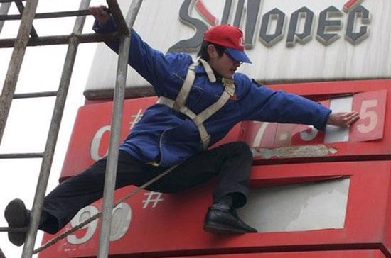 Nhân viên một trạm xăng tại Trung Quốc chỉnh sửa bảng giá. Thị trường hàng hóa thế giới diễn biến trái chiều theo số liệu lạc quan về kinh tế Mỹ - Ảnh: Reuters.