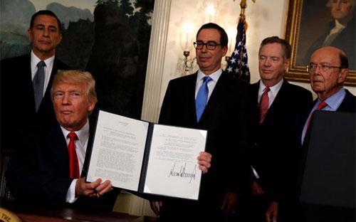 Tổng thống Mỹ Donald Trump và các quan chức Chính phủ nước này trong lễ ký biên bản ghi nhớ về rà soát các vấn đề thương mại Mỹ-Trung tại Nhà Trắng, ngày 14/8 - Ảnh: Reuters.<br>