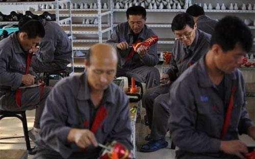 Công nhân người Triều Tiên đang làm việc trong một nhà máy sản xuất giày ở Dandong, Trung Quốc vào tháng 10/2012 - Ảnh: Reuters.<br>