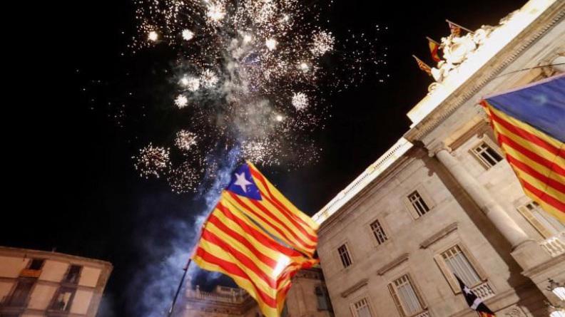 Người ủng hộ Catalonia độc lập treo cờ Catalonia và bắn pháo hoa trước tòa nhà nghị viện vùng này ngày 27/10 - Ảnh: Reuters.