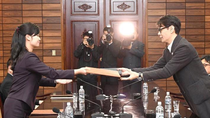 Đại diện Triều Tiên (trái) và đại diện Hàn Quốc trao đổi tài liệu tại cuộc đàm phán ở Panmumjom ngày 20/3 - Ảnh: Reuters.
