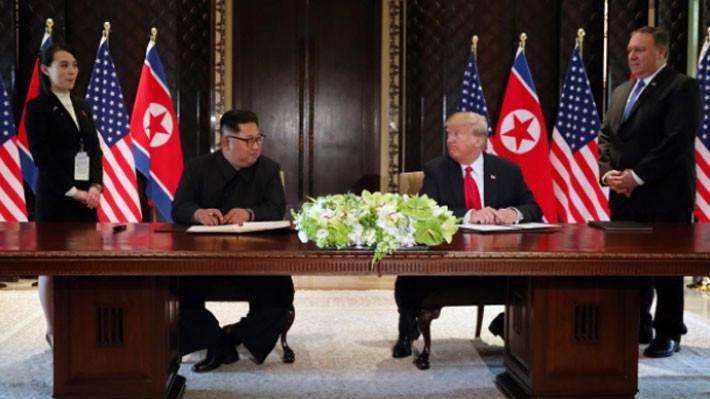 Nhà lãnh đạo Triều Tiên Kim Jong Un (trái) và Tổng thống Mỹ Donald Trump nhìn nhau trước khi đặt bút ký thỏa thuận tại Singapore ngày 12/6 - Ảnh: Reuters.