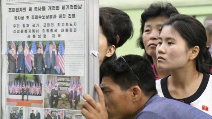 Người dân Triều Tiên đọc thông tin trên báo về thượng đỉnh Mỹ-Triều trên đường phố ở Bình Nhưỡng, ngày 13/6 - Ảnh: Kyodo/Reuters.