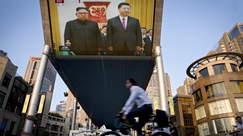 Một màn hình lớn phát hình ảnh nhà lãnh đạo Triều Tiên Kim Jong Un (trái) và Chủ tịch Trung Quốc Tập Cận Bình trên đường phố ở Bắc Kinh ngày 19/6 - Ảnh: AP/Bloomberg.