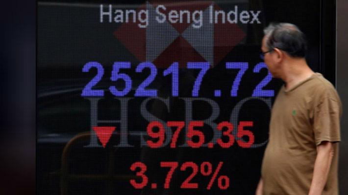 Một người đàn ông đi qua một bảng hiển thị chỉ số Hang Seng của thị trường chứng khoán Hồng Kông ở Hồng Kông, sáng 11/10 - Ảnh: Reuters.