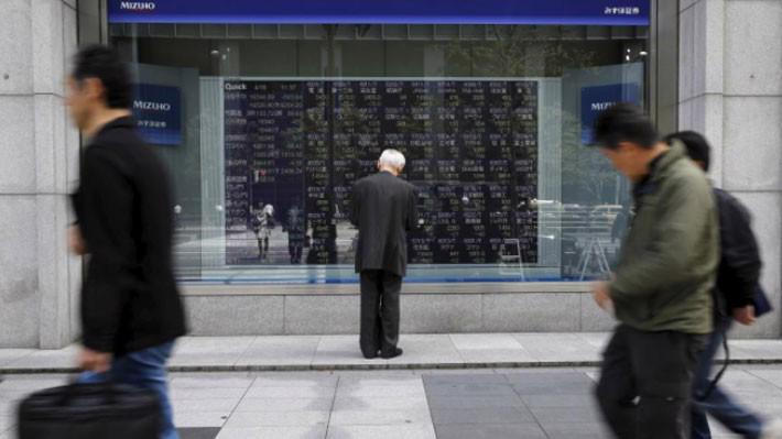 Một người đàn ông đứng xem bảng giá cổ phiếu trên đường phố ở Tokyo, Nhật Bản, tháng 4/2018 - Ảnh: Reuters.