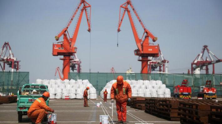 Các công nhân làm việc ở một bến cảng ở Thanh Đảo, Trung Quốc - Ảnh: Reuters.