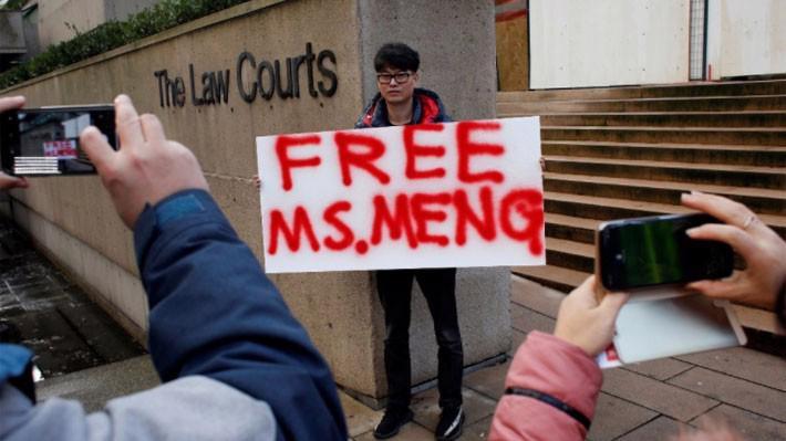 Một người giơ khẩu hiệu kêu gọi trả tự do cho bà Meng Wanzhou, CFO Huawei, trước tòa án ở Canada ngày 11/12 - Ảnh: Reuters.