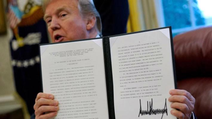 Tổng thống Mỹ Donald Trump và sắc lệnh mà ông ký về áp thuế quan lên máy giặt và tấm pin năng lượng mặt trời nhập khẩu vào Mỹ, tại Nhà Trắng, hôm 23/1/2018 - Ảnh: Reuters.