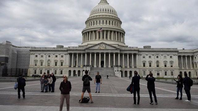 Du khách chụp ảnh trước tòa nhà Quốc hội Mỹ trên đồi Capitol ở Washington DC - Ảnh: Reuters.