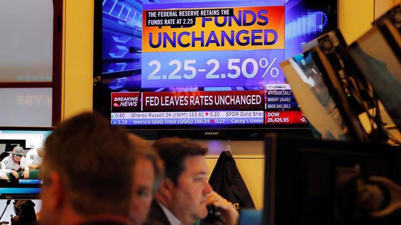Các nhà giao dịch cổ phiếu trên sàn NYSE ở New York, Mỹ, ngày 19/6. Một màn hình trên sàn giao dịch đang phát sóng bản tin về việc FED giữ nguyên lãi suất - Ảnh: Reuters.