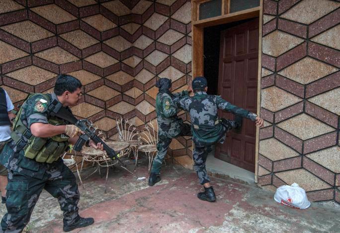 Binh sỹ quân đội Philippines đột kích vào một tòa nhà khi truy lùng phiến quân Maute ở thành phố Marawi - Ảnh: Reuters.<br>