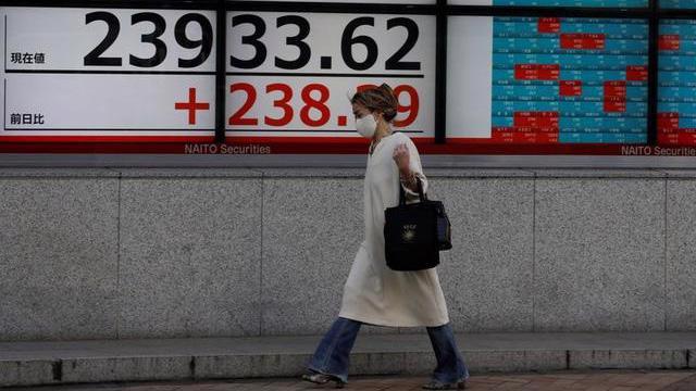 Một người bộ hành đi ngang qua một màn hình hiển thị mức điểm của chỉ số Nikki 225 trên đường phố ở Tokyo, Nhật Bản hôm 5/11 - Ảnh: Reuters.