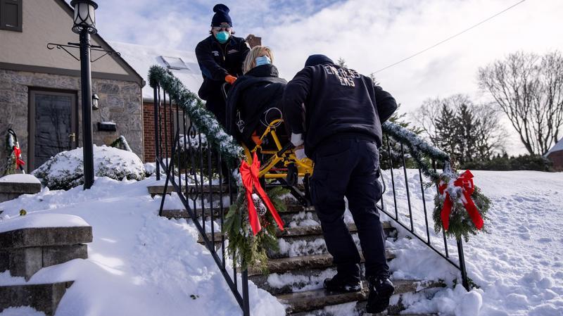 Hai nhân viên y tế đang đưa một phụ nữ có triệu chứng mắc Covid-19 tới bệnh viện ở Yonkers, New York, hôm 17/12 - Ảnh: Bloomberg.