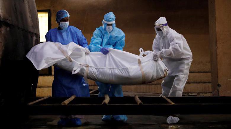 Các nhân viên y tế đang di chuyển thi thể một bệnh nhân Covid-19 ở Ấn Độ - Ảnh: Reuters.