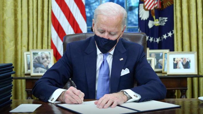 Tổng thống Mỹ Joe Biden ký các văn bản điều hành tại Phòng Bầu dục ngày 20/1 - Ảnh: Reuters.