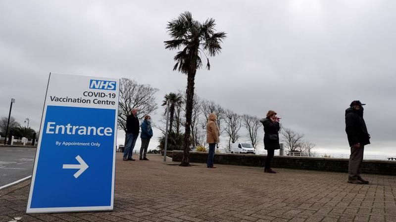 Người dân xếp hàng chờ tiêm vaccine Covid-19 tại một điểm tiêm chủng ở Anh - Ảnh: Reuters.