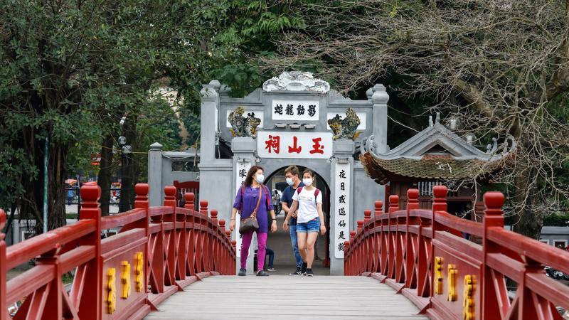 Du khách nước ngoài tại cầu Thê Húc, hồ Hoàn Kiếm, Hà Nội vào đầu tháng 3/2020 - Ảnh: Reuters