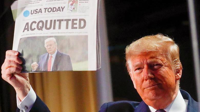 Tổng thống Mỹ Donald Trump giơ một tờ báo USA Today đưa tin ông được Thượng viện tha bổng trong cuộc luận tội đầu tiên, hôm 6/2/2020 - Ảnh: Reuters.