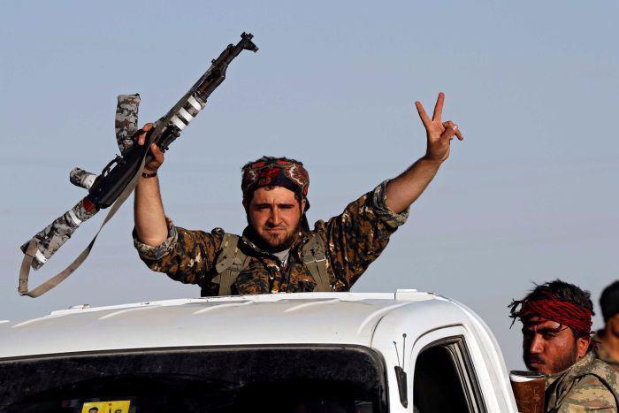 Một chiến binh SDF ăn mừng chiến thắng IS trên đường phố Raqqa ngày 17/10 - Ảnh: Reuters.<br>