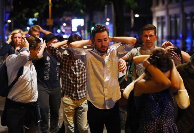 Đám đông rời khỏi hiện trường vụ tấn công khủng bố ở cầu London ngày 3/6 dưới sự hướng dẫn của cảnh sát - Ảnh: Reuters.<br>