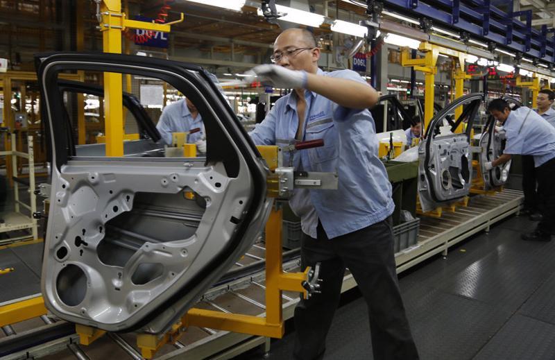 Công nhân làm việc trong một nhà máy liên doanh lắp ráp xe Ford ở Trùng Khánh, Trung Quốc.<br>