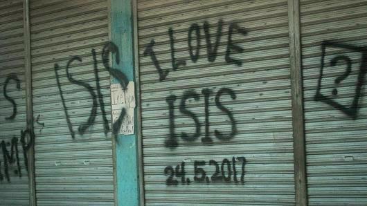 """Dòng chữ ghi """"tôi yêu ISIS [một tên gọi khác của tổ chức khủng bố IS]"""" trên bức tường một ngôi nhà ở Marawi, Philippines - Ảnh: Getty/CNBC.<br>"""