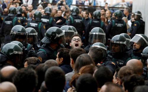 Cử tri Catalonia đụng độ với cảnh sát quốc gia Tây Ban Nha trong cuộc trưng cầu dân ý ngày 1/10 - Ảnh: Reuters.<br>